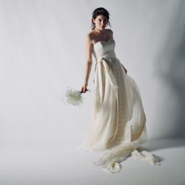 Un completo da sposa in stile principesco davvero romantico, composto da un abito con corsetto in seta molto essenziale e un top di pizzo a maniche corte, Mimosa.